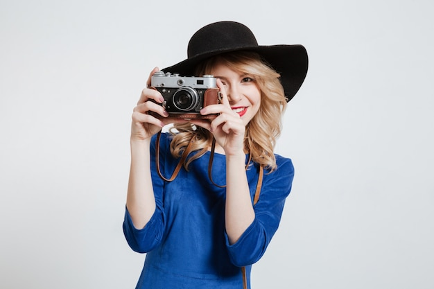 Amazing woman dressed in blue dress wearing hat holding camera