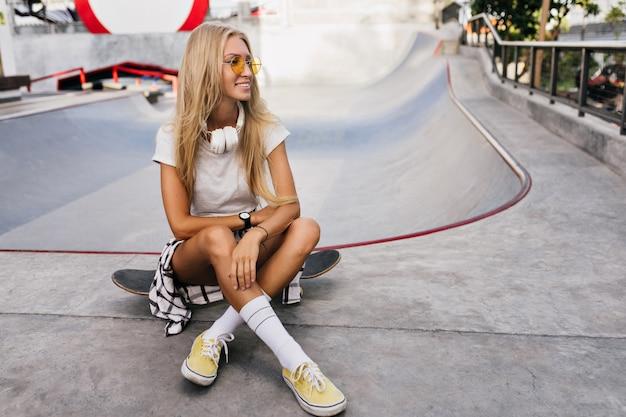 스케이트 보드에 앉아 큰 헤드폰에 놀라운 여자. longboard와 함께 포즈를 취하는 사랑스러운 금발 여성 모델의 야외 초상화.