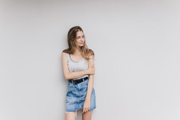Удивительная женщина в джинсовой юбке позирует в белой стене. крытый выстрел симпатичной девушки брюнетки изолированной с задумчивым выражением лица.