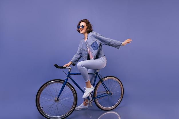 자전거에 앉아 봄 옷에 놀라운 여자. 장난하는 선글라스에 사랑스러운 여자의 실내 초상화.