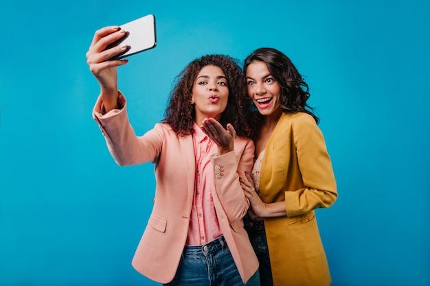 그녀의 친구가 사진을 찍는 동안 포즈 노란색 재킷에 놀라운 여자