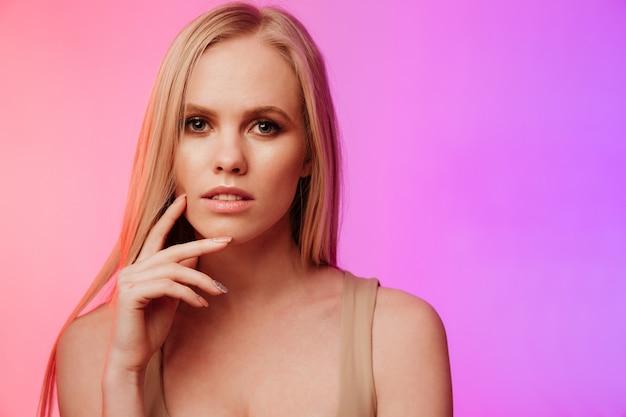 素晴らしい女性が立っているとピンクの壁を越えてポーズ