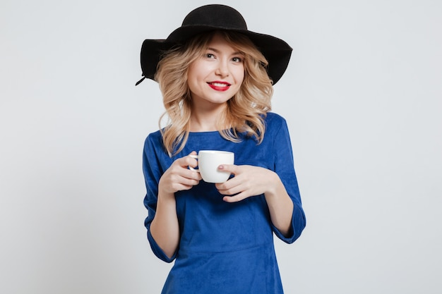 Amazing woman wearing hat holding cup of coffee
