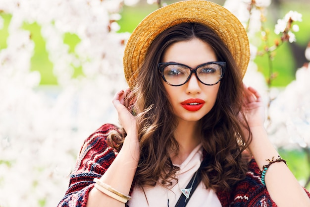 Amazing woman with bright make up, blue eyes, glasses, straw hat posing in sunny spring park near flower tree