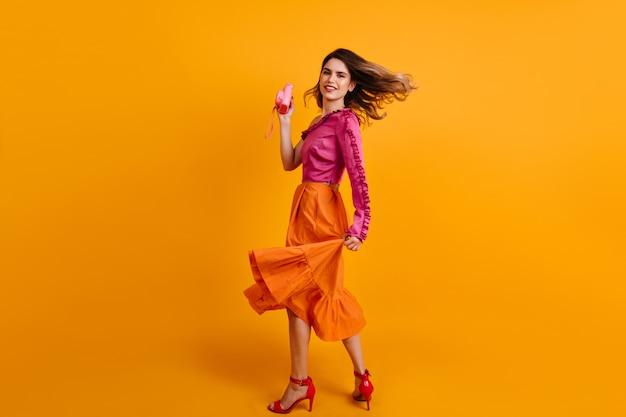 Удивительная женщина с камерой танцует в студии