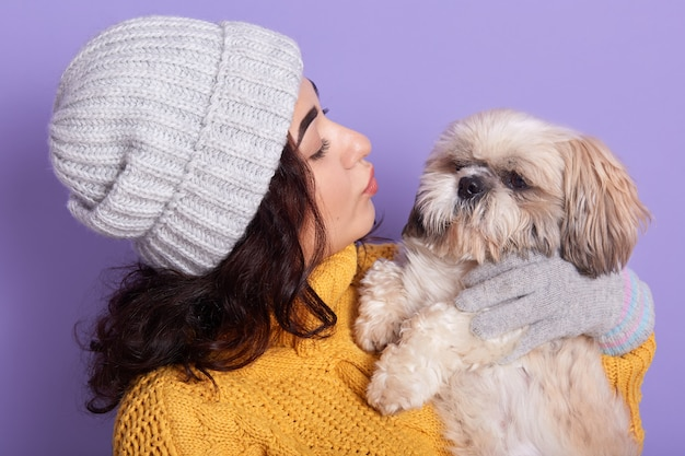 Amazing woman with dark wavy hair wants to kiss her little dog, attractive girl embracing her puppy isolated over purple wall