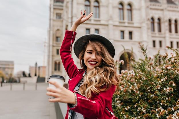 Incredibile donna con lunghi capelli ondulati scherzare per strada con una tazza di caffè