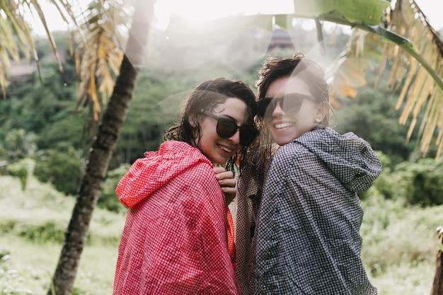 자연을 바라 보는 어두운 선글라스의 놀라운 여성. 이국적인 숲에서 시간을 보내는 여자 친구를 웃 고있다.