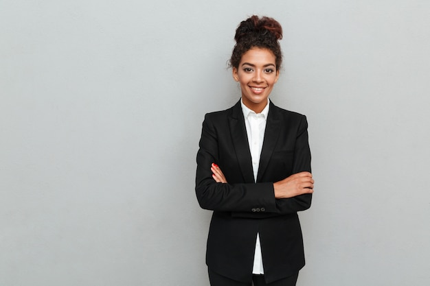 Amazing young african business woman standing over grey wall