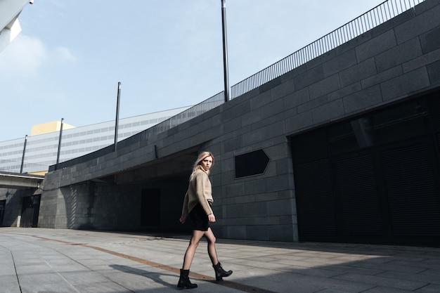 野外を歩いている素晴らしい若いブロンドの女性。よそ見。