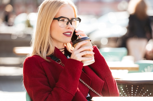 Amazing young caucasian woman talking by phone drinking coffee