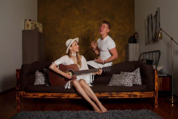 Удивительная молодая пара с гитарой в интерьере комнаты. милая женщина и мужчина на софе с гитарой. концепция домашнего обучения или игры на гитаре дома. место, защищенное авторскими правами для сайта, баннера или логотипа