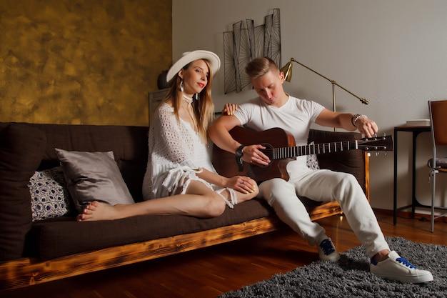 방의 내부에 기타와 함께 놀라운 젊은 부부. 귀여운 여자와 기타와 함께 소파에 남자
