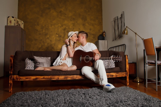 Amazing young couple with guitar in interior of room. cute woman and man on sofa with guitar