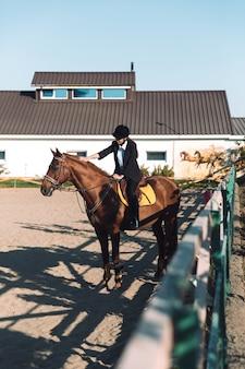 Удивительная молодая пастушка сидит на лошади на открытом воздухе