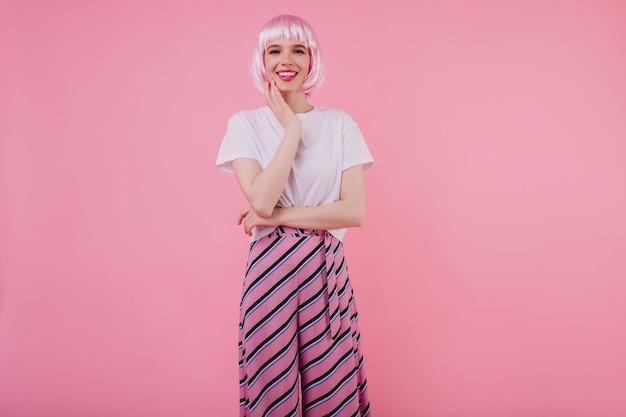 トレンディなペルークの驚くべき若い女性が笑顔で彼女の頬に触れています。白いtシャツとピンクのかつらで洗練された白人女性の屋内肖像画
