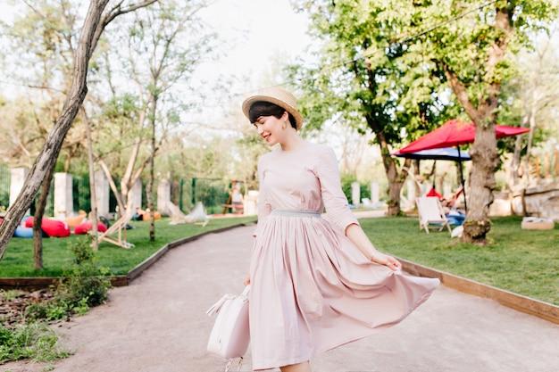 Удивительная девушка играет со своим длинным светло-фиолетовым платьем, гуляя по парковой аллее перед пикником с друзьями
