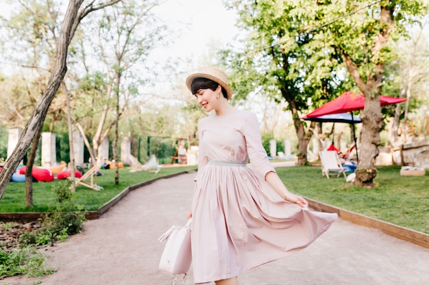 Amazing young lady playing with her long light-purple dress, walking in park alley before picnic with friends