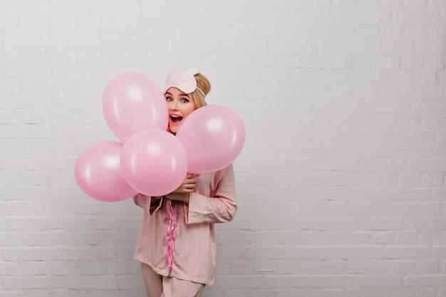 Incredibile giovane donna indossa un pigiama di seta per festeggiare il compleanno. ritratto di ragazza adorabile in sleepmask holding palloncini isolati su parete leggera.
