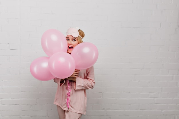 Удивительная барышня в шелковой пижаме отмечает день рождения. портрет очаровательной девушки в маске сна, держа воздушные шары, изолированные на светлой стене.