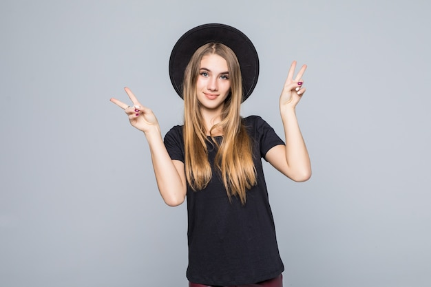Amazing young lady with gold hair dressed up in black with retro hat shows victory sign isolated on background