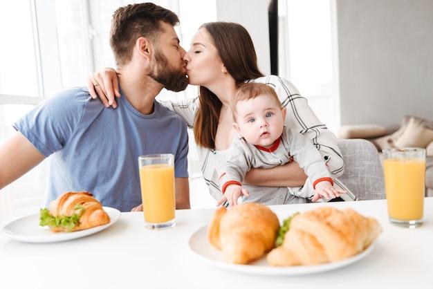 彼らの小さな赤ちゃんを持つ素晴らしい若い愛するカップル両親