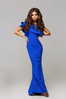 スタジオでポーズをとってエレガントな青いイブニングドレスの素晴らしい若いモデル
