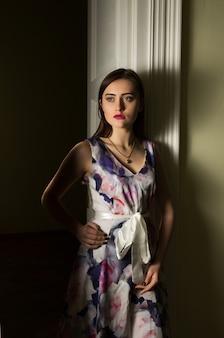 暗い部屋でポーズをとって、長いドレスを着てプロのメイクで素晴らしい若いモデル