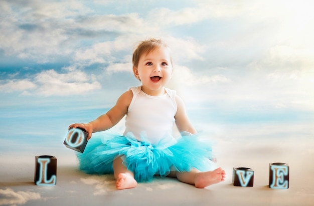 Amazing young smiling little girl in a blue full skirt rejoices and sits in the sky among clouds and sunlight with cubes with letters love. the concept of cute and naive children