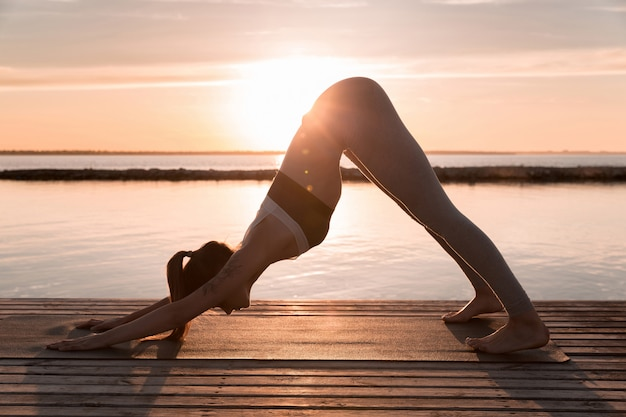 Удивительная молодая спортивная леди делает упражнения йоги.
