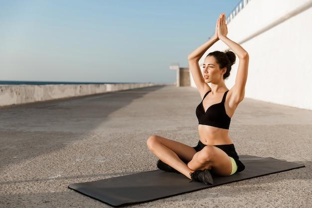 驚くべき若いスポーツの女性は、ビーチで屋外でヨガの練習を瞑想させます。