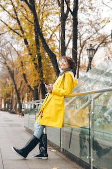 Amazing young woman dressed in raincoat