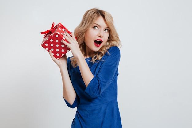 흰 벽에 선물 상자를 들고 놀라운 젊은 여자
