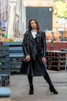 Defocused 야외 카페 벽에 검은 가죽 옷에 놀라운 젊은 여자