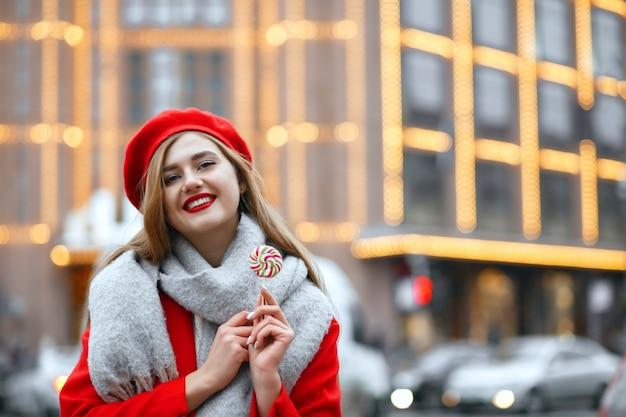 甘いお菓子を保持している赤いコートの素晴らしい若い女性。空きスペース