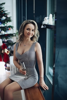 Amazing young woman keeping smile on her face while having photo session in festive dress