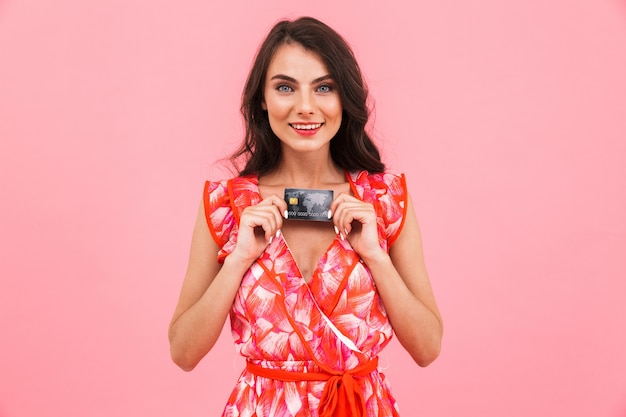 クレジットカードを保持している孤立した壁をポーズする驚くべき若い女性。