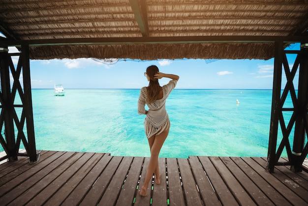 まっすぐ見て日よけの下のビーチでリラックスできる素晴らしい若い女性