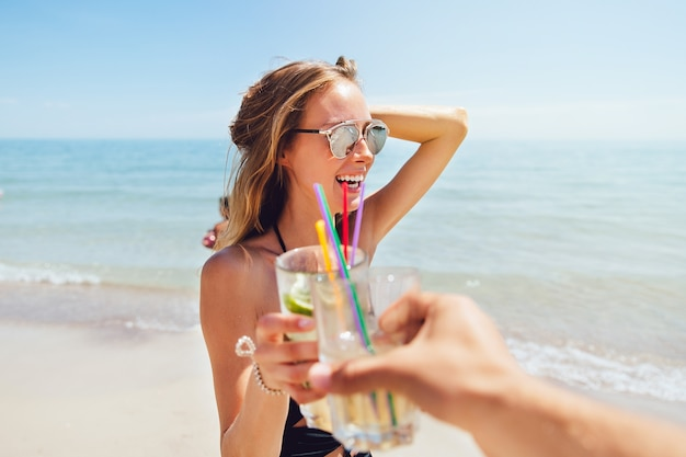 Amazing young woman in swimsuit and sunglasses, drinking a cocktail, toasting