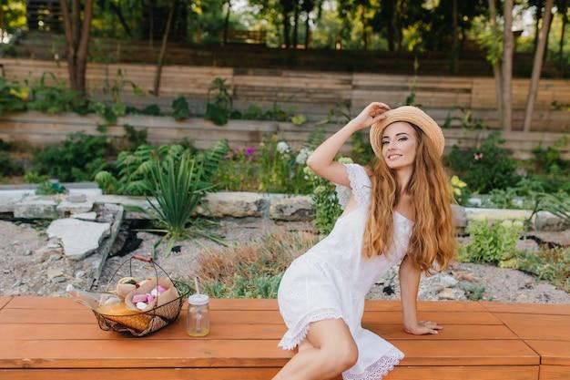 Incredibile giovane donna con i capelli castano chiaro in posa mentre tocca il cappello vintage e sorridente. splendida ragazza in abito bianco alla moda seduto vicino a un'aiuola con cestino da picnic.