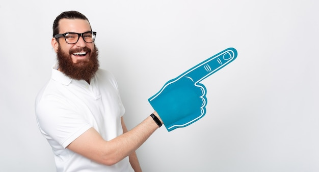 An amazingly happy bearded man is smiling at the camera holding a blue fan glove pointing with it at a free space