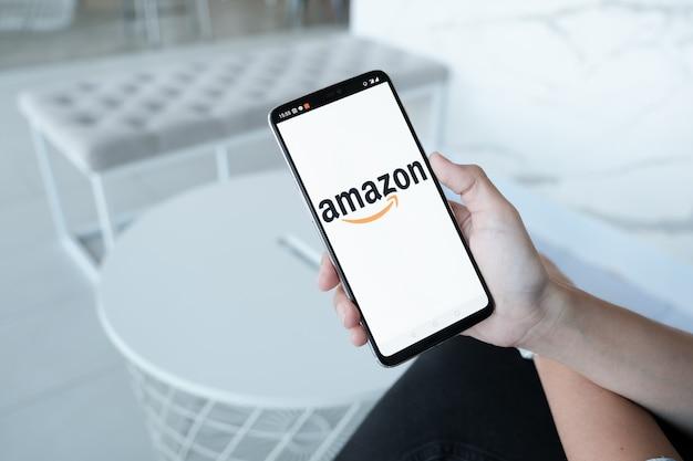 オンラインショッピングにamazonロゴを表示するスマートフォン。 amazon.com、inc.アメリカの国際的な電子商取引会社。