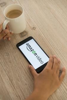 Руки с смартфоном, показывающие приложение для видеоадаптера amazon