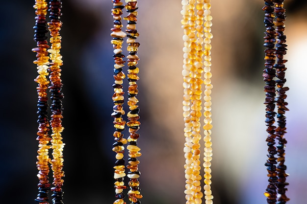 Amber background of beads and necklaces at the handicraft market. traditional souvenirs from baltic countries