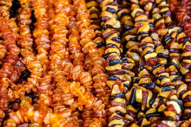Янтарные бусы разных цветов для продажи на уличном рынке