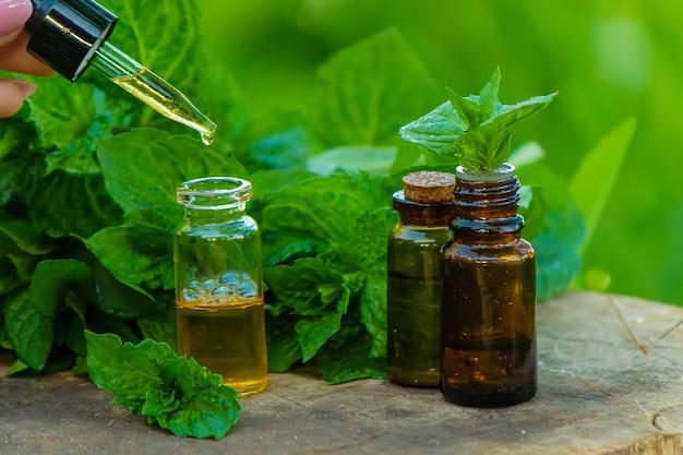 エッセンシャルオイル入りの琥珀色のボトルペパーミントとフレッシュミントの葉、濃いガラスの瓶に入ったハーブの香り。アロマテラピーのコンセプト。セレクティブフォーカス