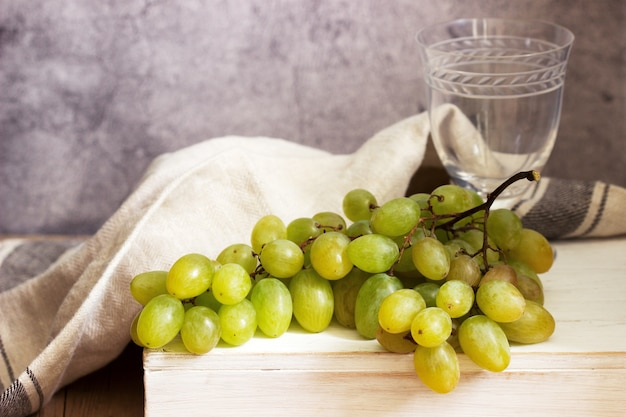 Янтарная гроздь винограда на сером бетоне