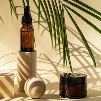 木製の幾何学的な台座にピペット付きの琥珀色の化粧品ボトル