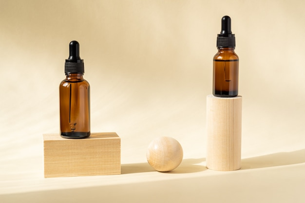 Amber cosmetic bottles with pipette on wooden geometric pedestal podiums