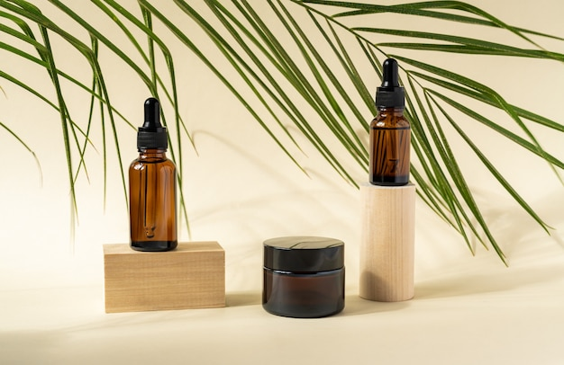Amber cosmetic bottles with pipette on wooden geometric pedestal